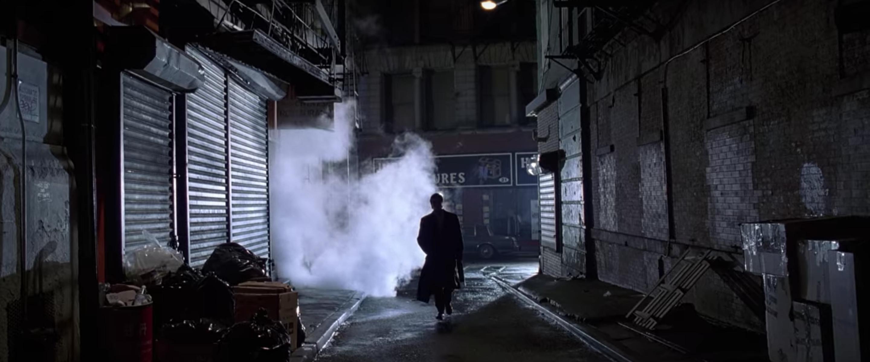 Bateman walks down alleyway.
